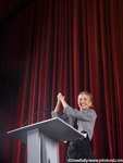 Picture of a woman on the stage of a theater behind a gray podium having just finished a speech. She has her hands clasped together and held up high as a sign of victory or winning.